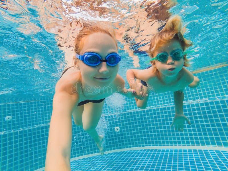 Pys som lär att simma i en simbassäng, moder som rymmer barnet arkivbilder