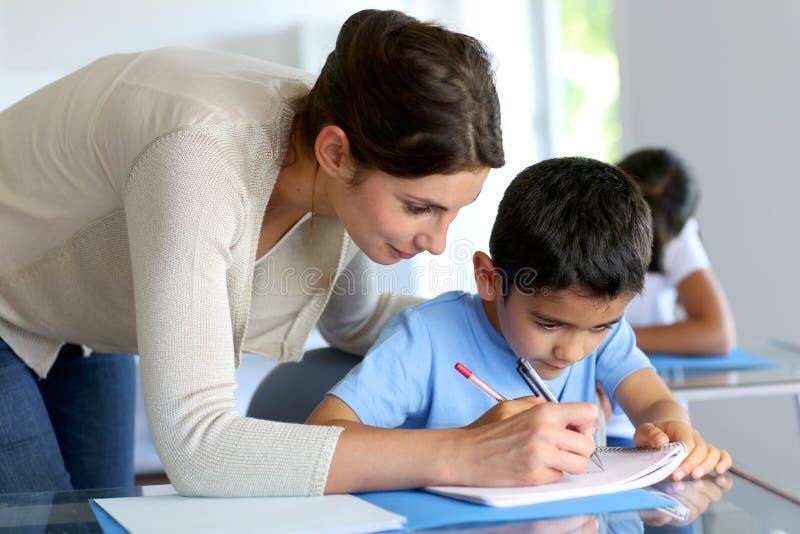 Pys som lär hur man skriver med läraren royaltyfri fotografi