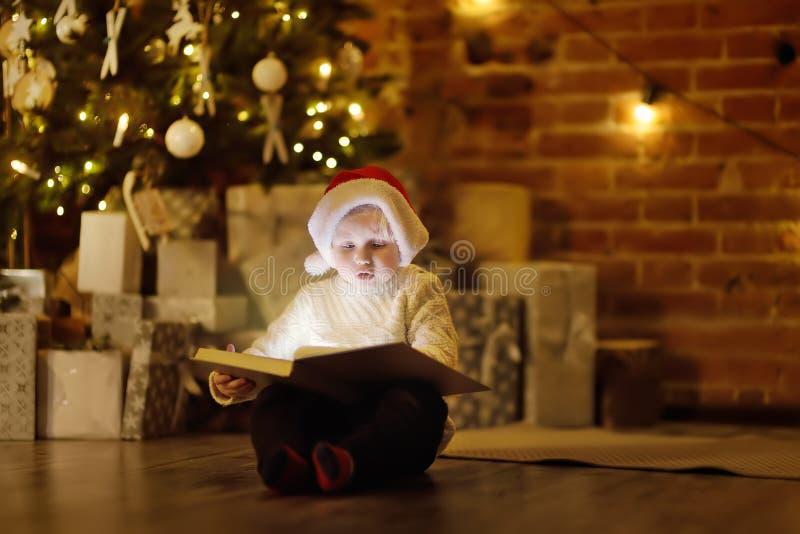 Pys som läser en magisk bok i dekorerad hemtrevlig vardagsrum Stående av den lyckliga ungen på julhelgdagsafton arkivfoton