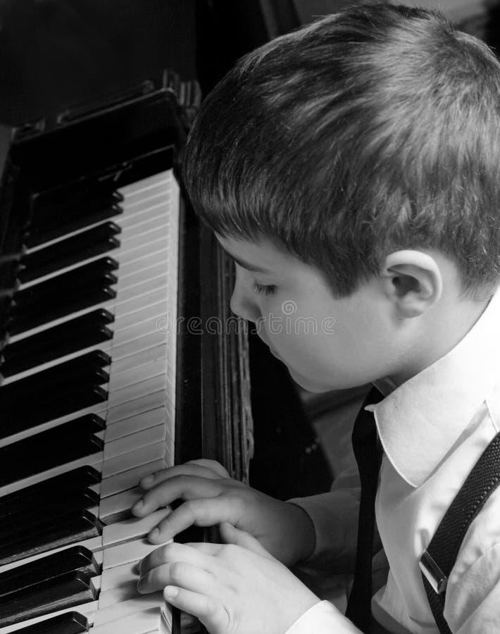 pojke som leker pianot arkivfoton