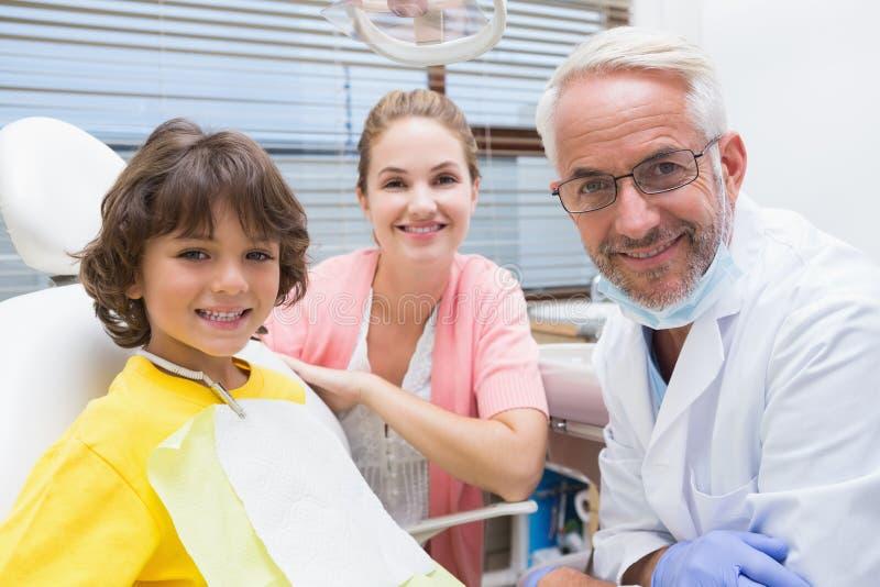 Pys som ler på kameran med modern och tandläkaren bredvid honom royaltyfri bild