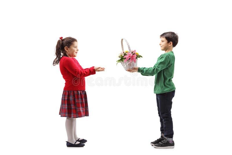 Pys som lite ger en korg med blommor till flickan royaltyfri bild