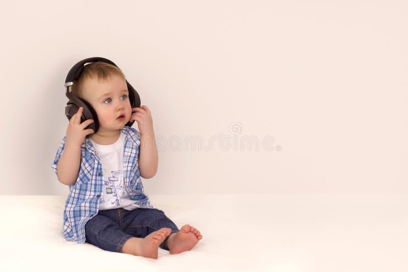 Pys som lyssnar till musik på hörlurar royaltyfria foton