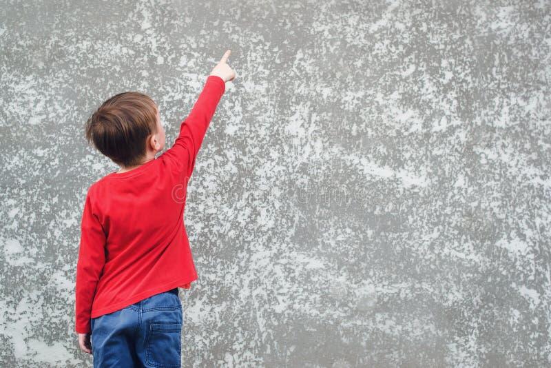 Pys som pekar på tomt ställe på betongväggen Tillbaka sikt av barnet Kall pojke som bär den röda skjortan och jeans Modell Barnet royaltyfri bild