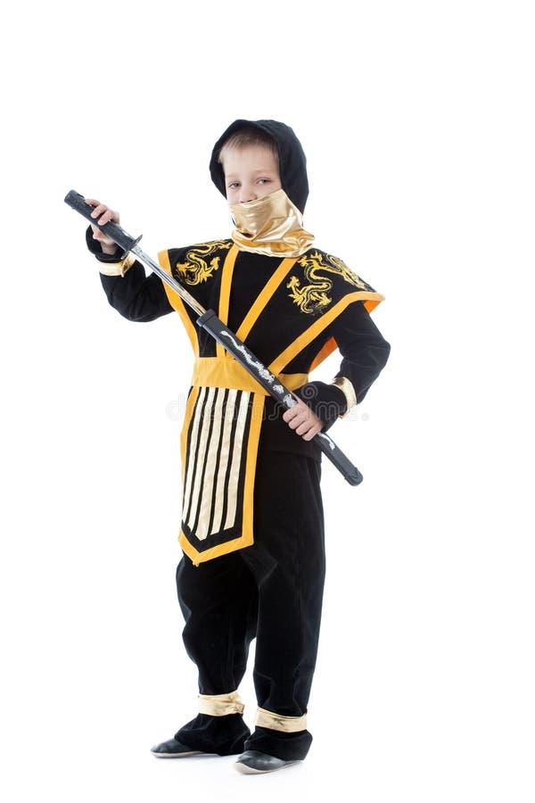 Pys som poserar i ninjadräkt med katana arkivfoton