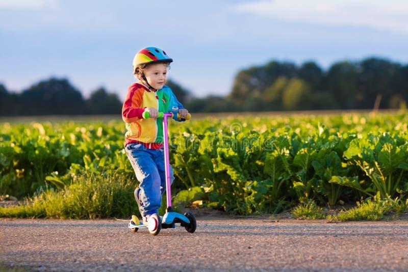 Pys som rider en färgrik sparkcykel royaltyfria bilder