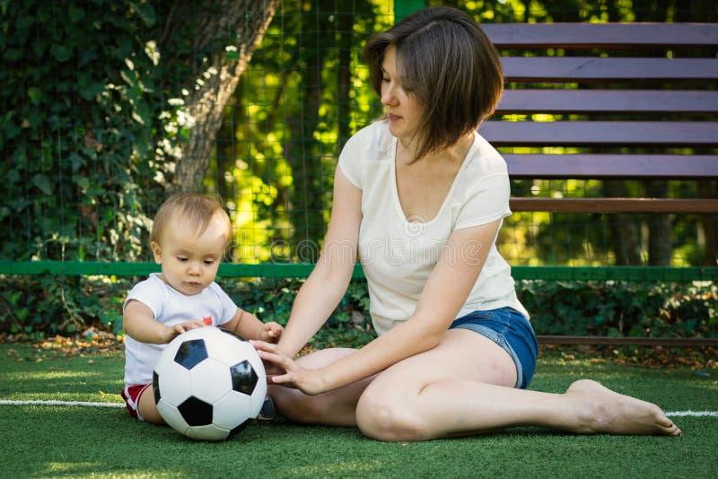 Pys som ser fotbollbollen och undersöker den som sitter bredvid moder på fotbollfältet Litet barnson som spelar med mamman utomhu arkivfoton
