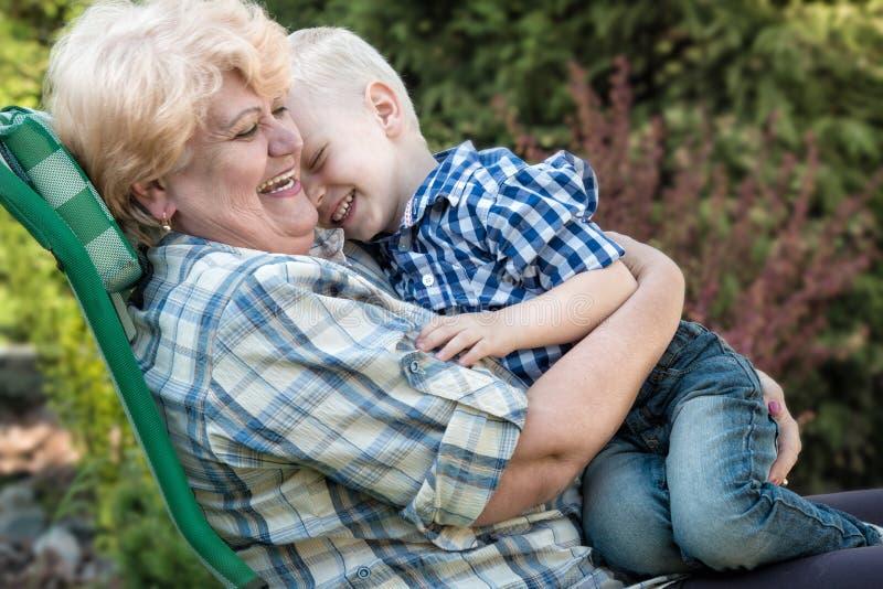 Pys som sitter på armarna av hans älskade farmor Kyssar och försiktiga kramar Förälskelseutvecklingar royaltyfri bild