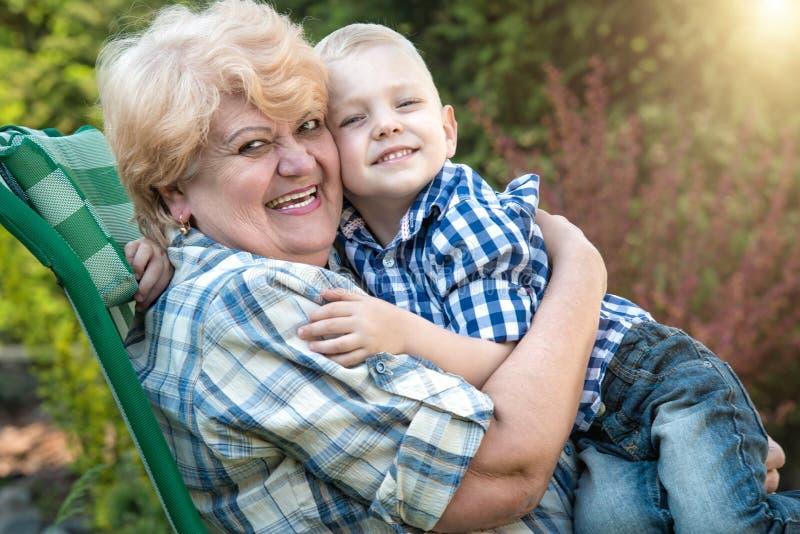 Pys som sitter på armarna av hans älskade farmor Kyssar och försiktiga kramar Förälskelseutvecklingar arkivfoto
