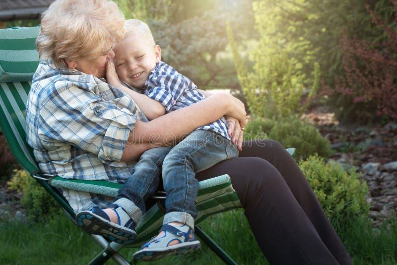 Pys som sitter på armarna av hans älskade farmor Kyssar och försiktiga kramar Helg i ett landshus royaltyfri fotografi