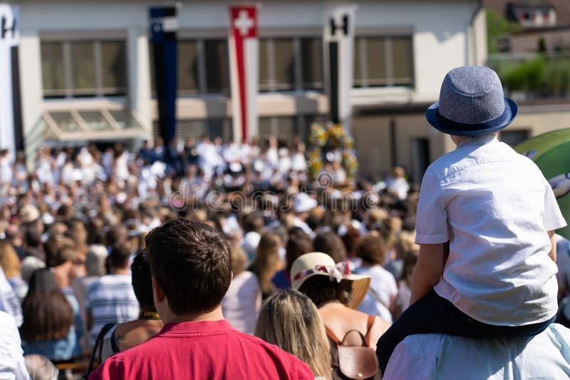 Pys som sitter på skuldran och hållande ögonen på skolbarn som sjunger på Jugendfest Brugg Impressionen arkivfoto
