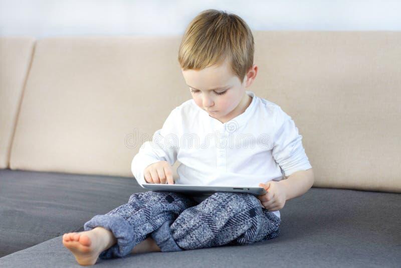 Pys som sitter på soffan på vardagsrummet och använder pekskärmminnestavlan Lyckligt smart barn som spelar leken på minnestavlada royaltyfri fotografi