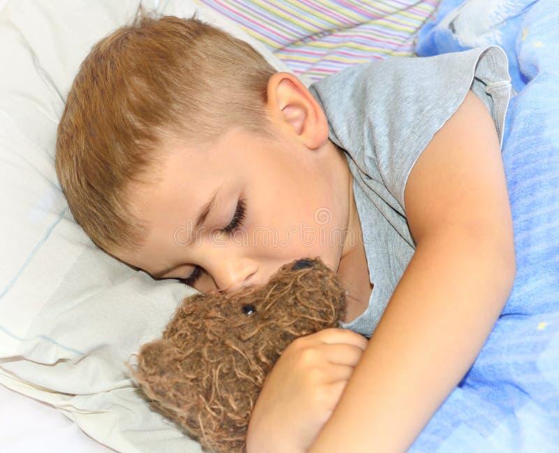 Pys som sover med hans nallebjörn royaltyfri foto