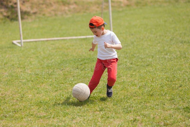 Pys som sparkar bollen i parkera spela fotbollfotboll i parkera sportar för övning och aktivitet arkivfoto
