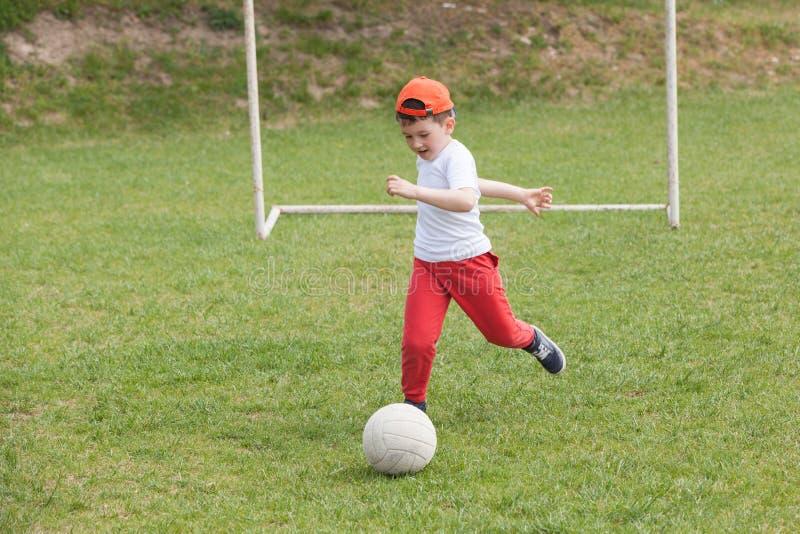 Pys som sparkar bollen i parkera spela fotbollfotboll i parkera sportar för övning och aktivitet royaltyfri bild