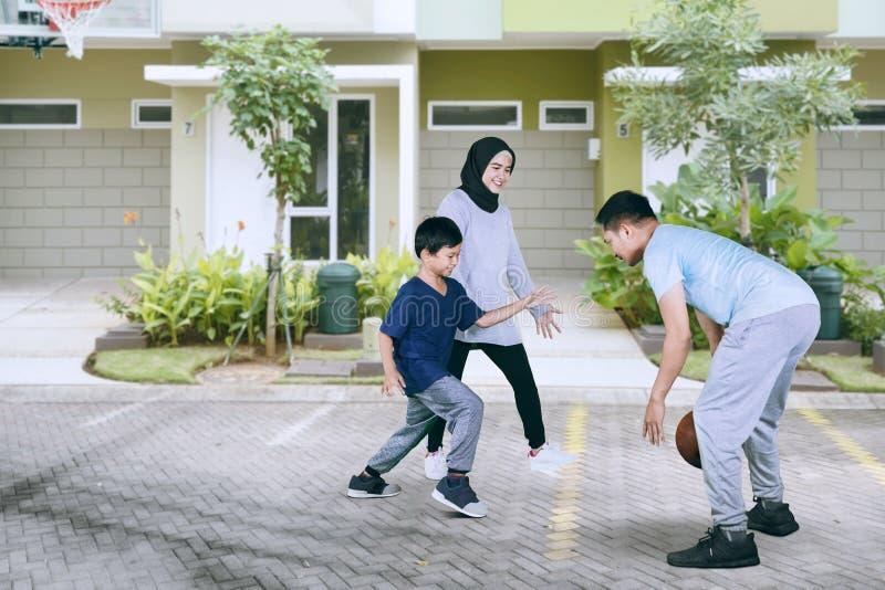Pys som spelar basket med hans föräldrar arkivbilder