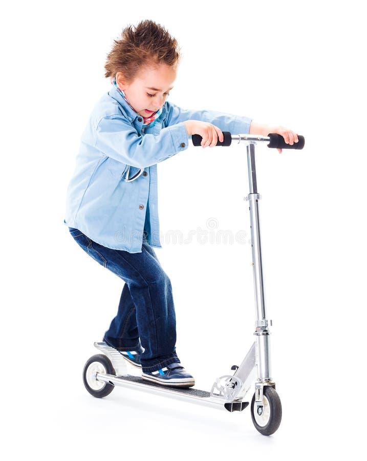 Pys som spelar med hans sparkcykel royaltyfria foton