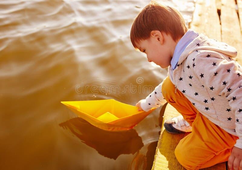 Pys som spelar med leksakpappersskeppet vid sjön royaltyfri fotografi
