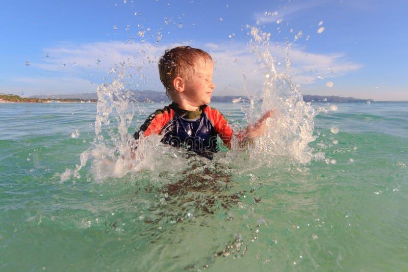 Pys som spelar med vatten på stranden royaltyfri bild