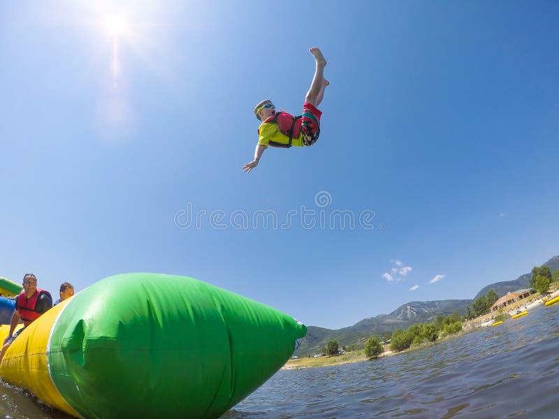 Pys som spelar på den uppblåsbara vattenleksaken på sjön royaltyfria foton