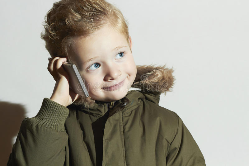 Pys som talar på mobiltelefonen modernt barn i vinterlag Dana ungar Barn arkivfoto