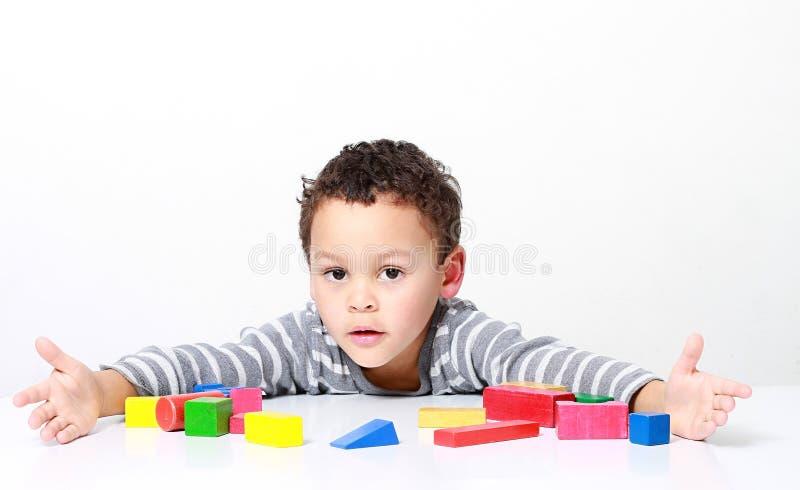 Pys som testar hans kreativitet, genom att bygga torn med leksakbyggnadskvarter royaltyfri foto