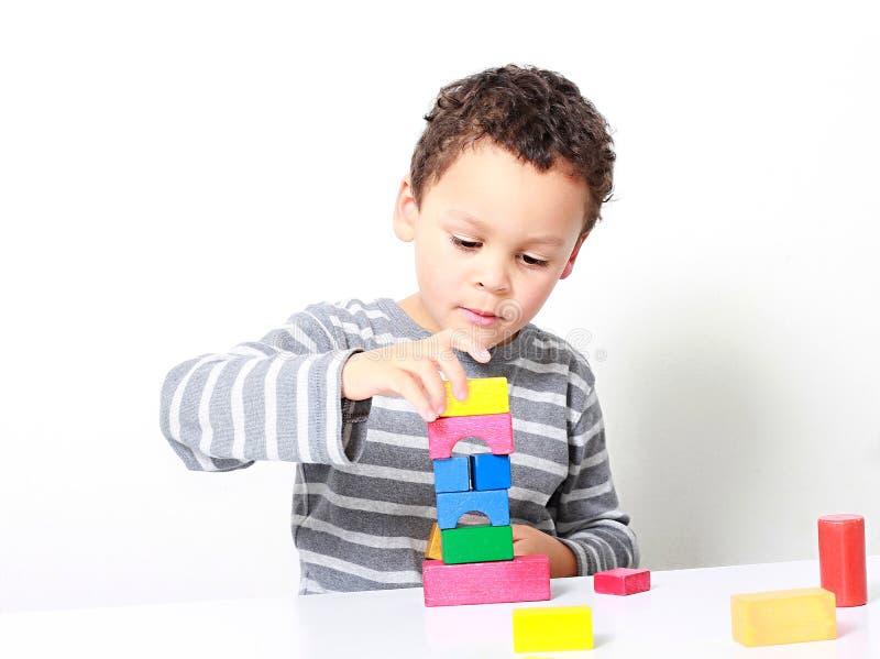 Pys som testar hans kreativitet, genom att bygga torn med leksakbyggnadskvarter arkivfoto