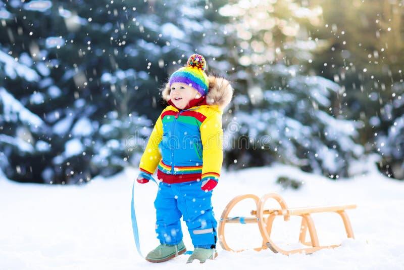 Pys som tycker om en släderitt Sledding för barn Litet barnunge som rider en pulka Barnlek utomhus i snö Ungesläde i arkivfoto
