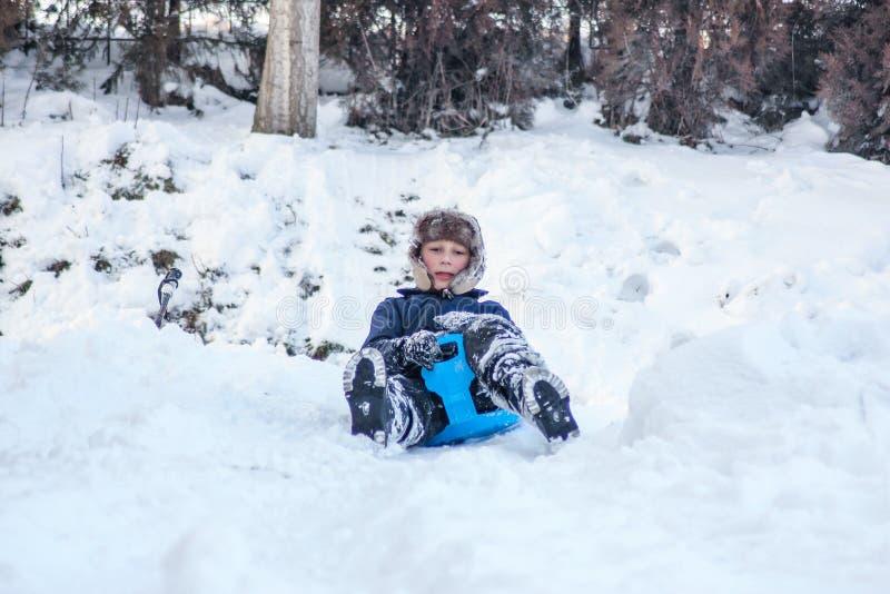 Pys som tycker om en sl?deritt Sledding f?r barn Litet barnunge som rider en pulka Barnlek utomhus i sn? Ungesl?de i royaltyfri bild