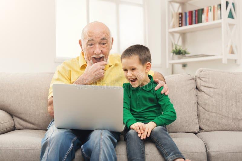 Pys som undervisar hans farfar att använda bärbara datorn arkivfoton