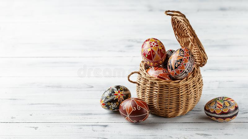 Easter eggs decorated with wax resist technique. Pysanky in the basket, Ukrainian Easter eggs decorated with wax-resist dyeing technique, white wooden background stock photos