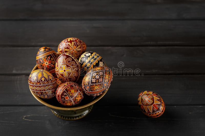 Easter eggs decorated with wax resist technique. Pysanky in a bowl, Ukrainian Easter eggs decorated with wax-resist dyeing technique, black wooden background royalty free stock images
