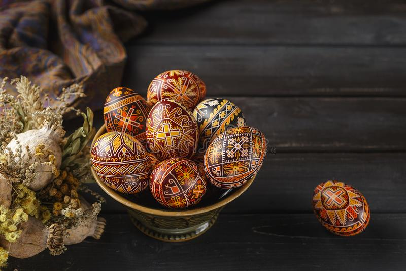 Easter eggs decorated with wax resist technique. Pysanky in a bowl, Ukrainian Easter eggs decorated with wax-resist dyeing technique, dry flowers, black wooden royalty free stock image