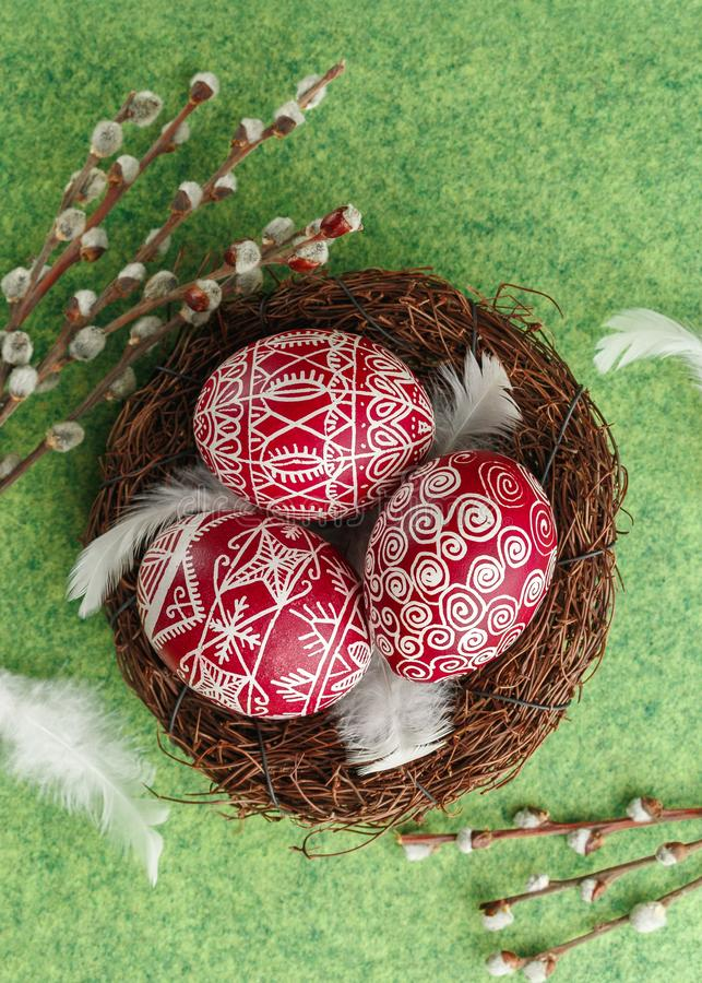 Pysanky, decorated Easter eggs in the nest. Willow branches and white feathers on green background, wide format, top view, copy space royalty free stock images