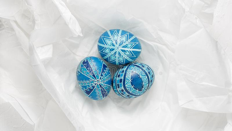 Pysanky on the white crumpled paper background. Easter eggs decorated with wax-resist dyeing technique, traditional for Eastern European countries, wide format stock photography