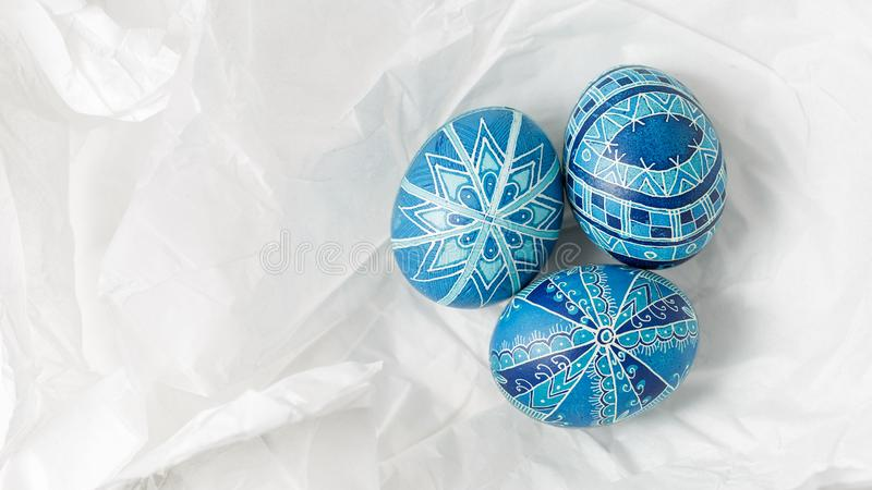 Pysanky on the white crumpled paper background. Easter eggs decorated with wax-resist dyeing technique, traditional for Eastern European countries, wide format royalty free stock photography