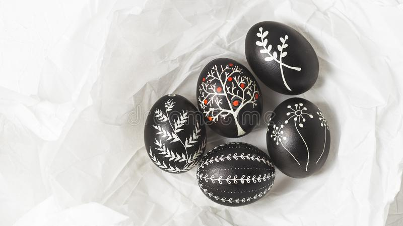 Pysanky on the white crumpled paper background. Easter eggs decorated with wax-resist dyeing technique, traditional for Eastern European countries, wide format stock images