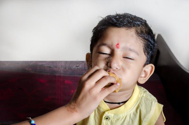 pysbarn som äter sötsaker med stängda ögon som tycker om delen royaltyfri foto