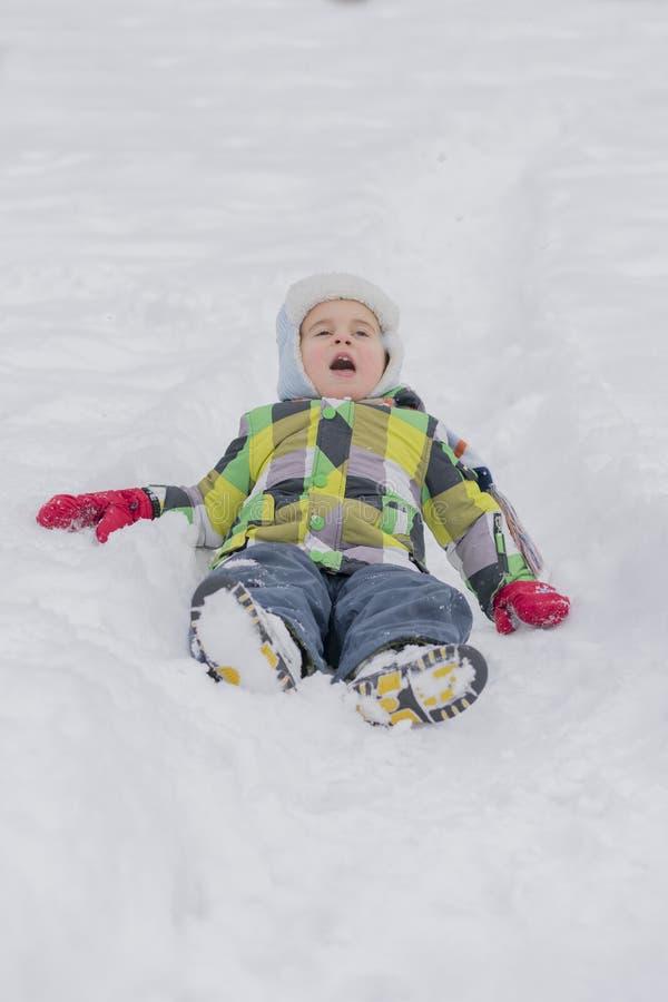 Pysbarn som spelar med snö och har gyckel som ligger på snöig fält och utomhus gör snöängel i kall vinterdag Barn royaltyfri fotografi
