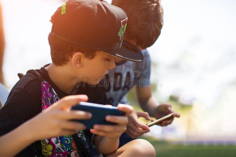 Pysbarnet som spelar mobilen, spelar p? smartphonen i parkera arkivfoto