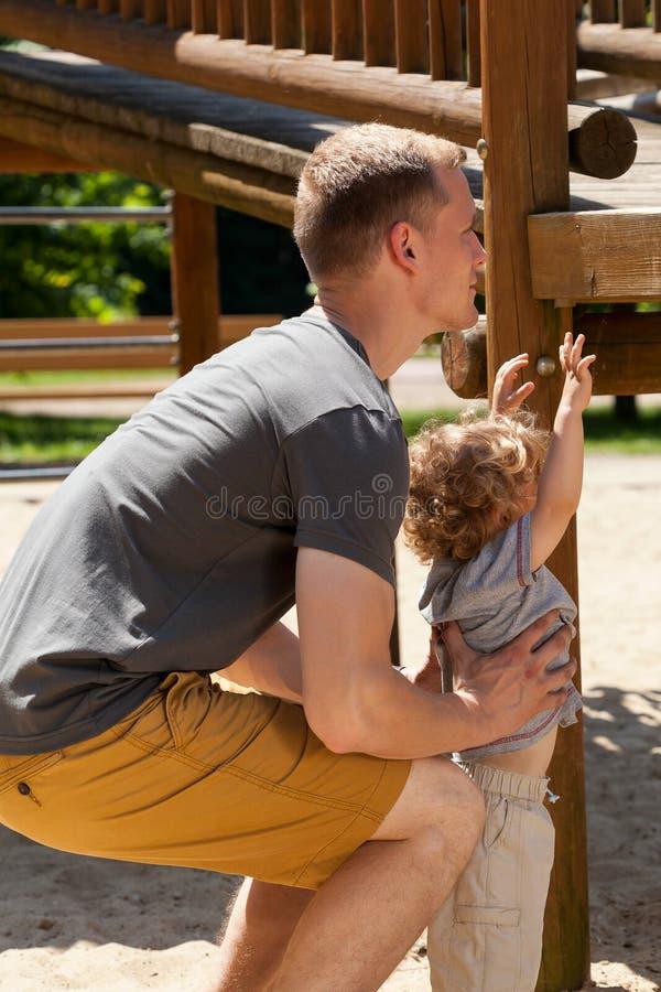 Pysen behöver faderns hjälp royaltyfri foto