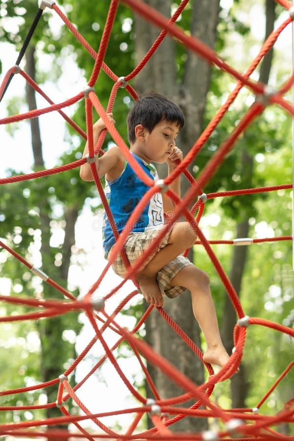 Pysen brunetten som bär blåa t-skjorta och kortslutningsklättringrep på lekplatsen i, parkerar i sommaren arkivbild