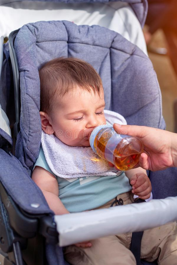 Pysen dricker fruktsaft från en flaska, medan sitta i en barnvagn arkivbild