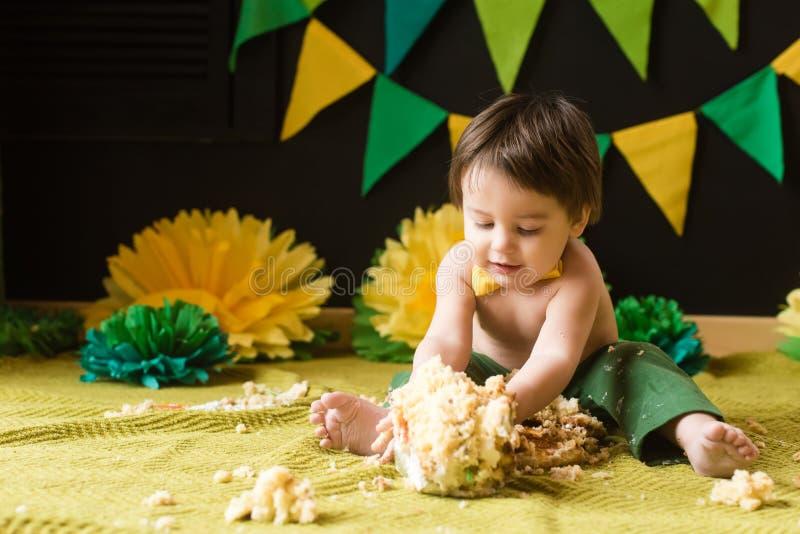 Pysen förstör totalt hans första födelsedagkaka royaltyfria foton
