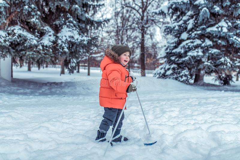 Pysen 3-4 gamla år, vinterbarn skidar, lyckliga le lekar och att ha rolig aktiv bild av barn Bakgrund royaltyfri foto
