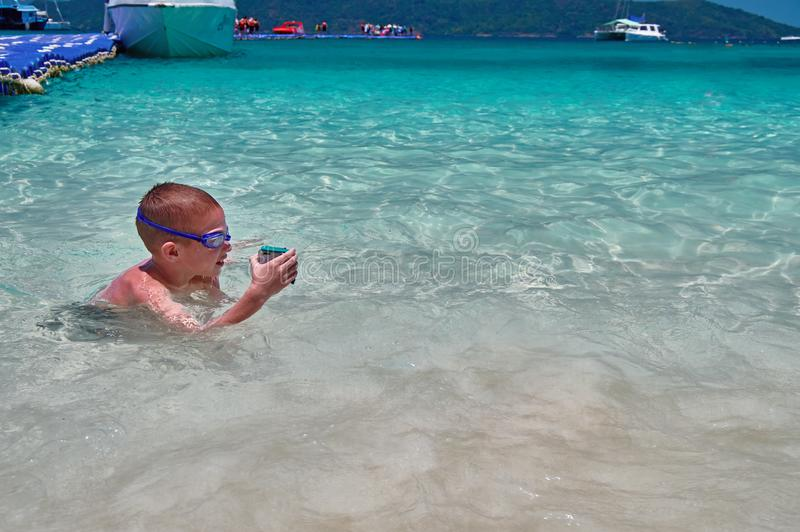 Pysen, i att simma exponeringsglas, spelar i turkosvatten med handlingkameran i skyddande ask Barnet simmar i det tropiska havet  royaltyfri foto