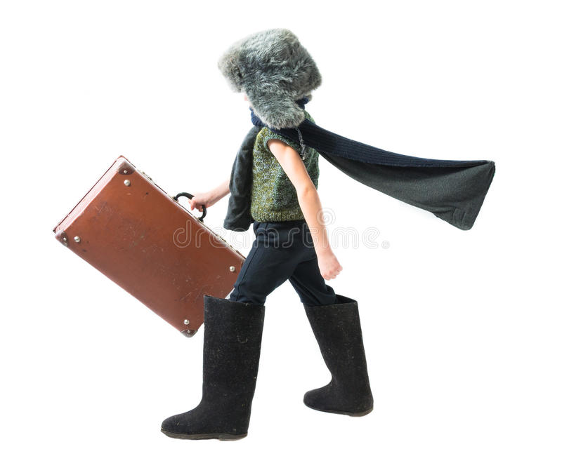 Pysen i en pälshatt och filt startar purposefully rörande framåtriktat med den framkallande halsduken och rymmer den gamla resväs royaltyfri foto