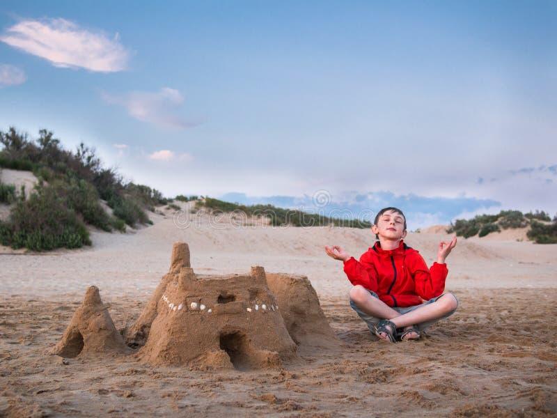 Pysen i kortslutningar och ben för ett omslagssammanträde som korsas nära den sandiga slotten och, mediterar mot den blåa himlen  royaltyfria bilder