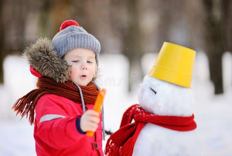 Pysen i röd vinterkläder som har gyckel med snögubben i snöig, parkerar arkivfoton