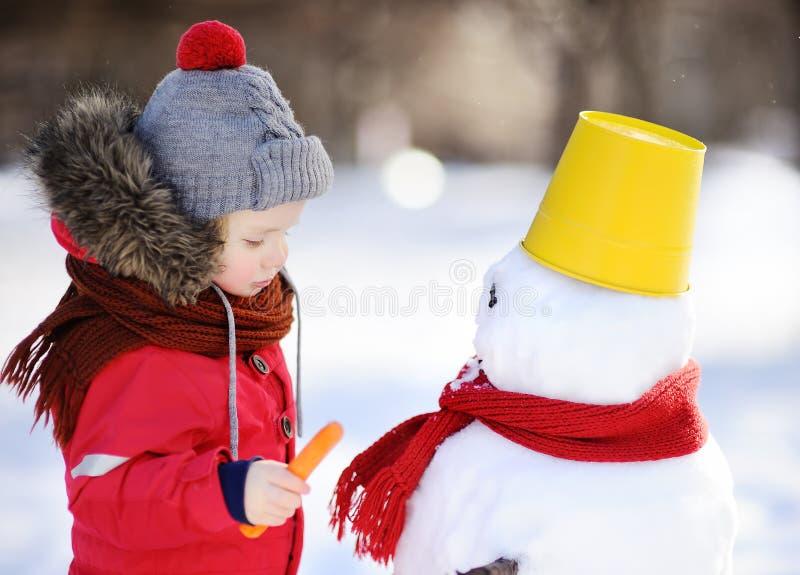 Pysen i röd vinterkläder som har gyckel med snögubben i snöig, parkerar arkivbild